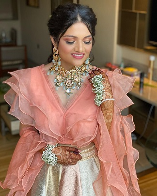 Ruffled blouse in peach with kundan jewelry for Indian bride