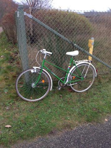 green bike on fence