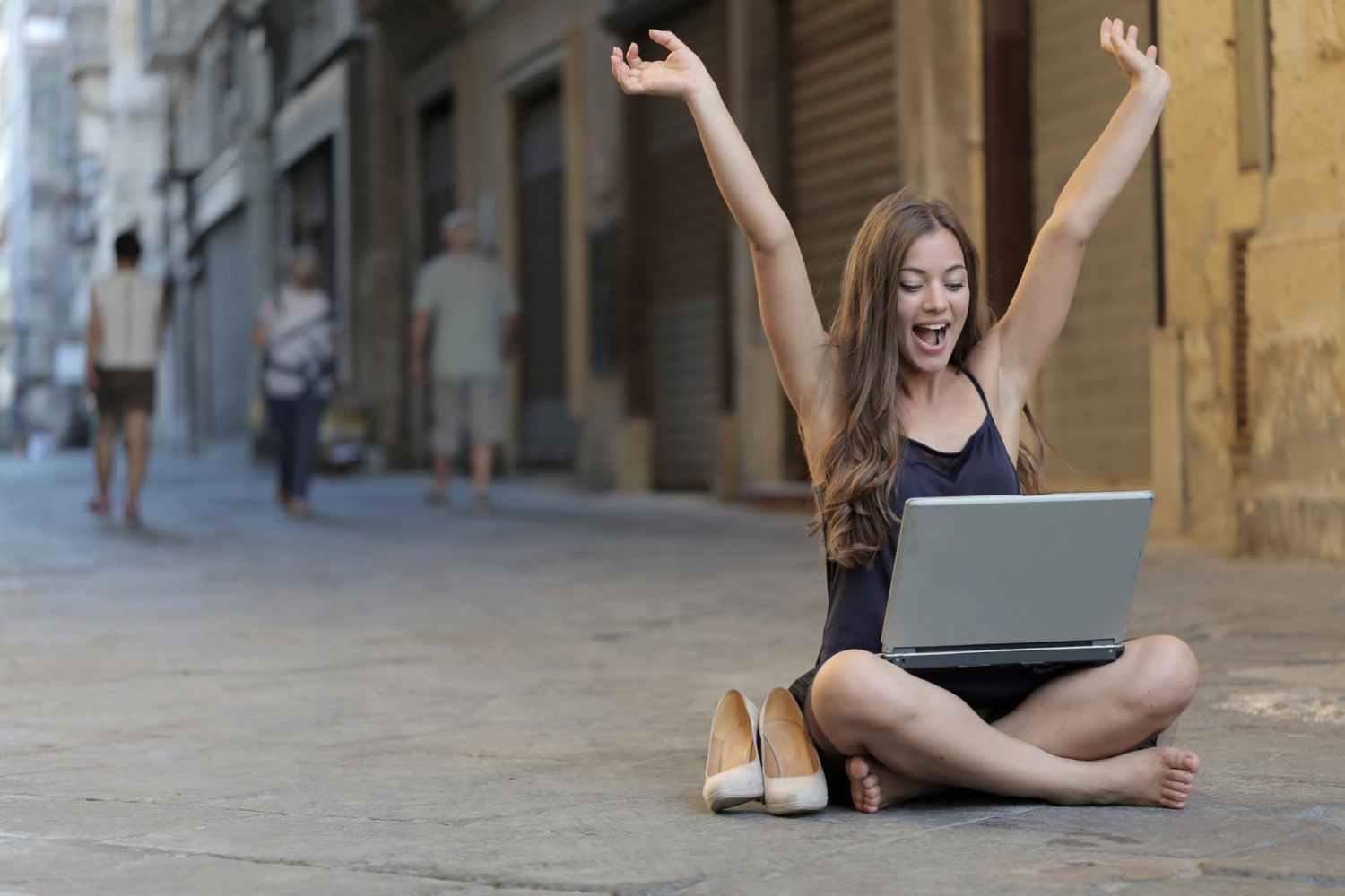 woman raising her hands up while sitting on floor with macbook pro on lap