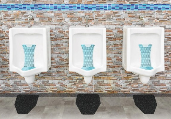 Clean Splash Hog Vertical Urinal Screens With Black Original Cut Antimicrobial Urinal Mats From WizKid Products Installed In A Public Restroom