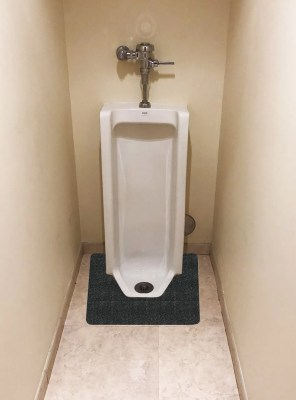 Black WizKid Products Square Nose Floor Mount Antimicrobial Urinal Mat Installed In Front Of A Commercial Floor Mount Urinal In Public Restroom
