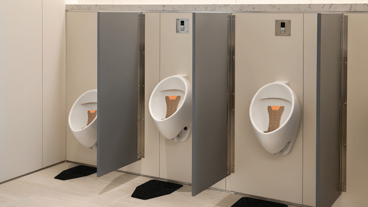 WizKid Products Mango Mini Splash Hog Vertical Urinal Screens and WizKid Original Cut Antimicrobial Mats Installed In A Public Restroom