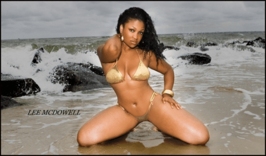 Kyra-Chaos-kneeling-in-the-water-showing-off-her-sexy-curves-in-a-gold-bikini-in-her-shoot-with-Lee-McDowell