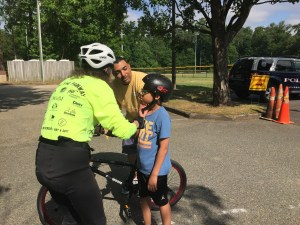 Mrs. Mary Turnbull of BikeWalk Williamsburg gives a helmet lesson to a Bike Rodeo participant at the Quarterpath site.