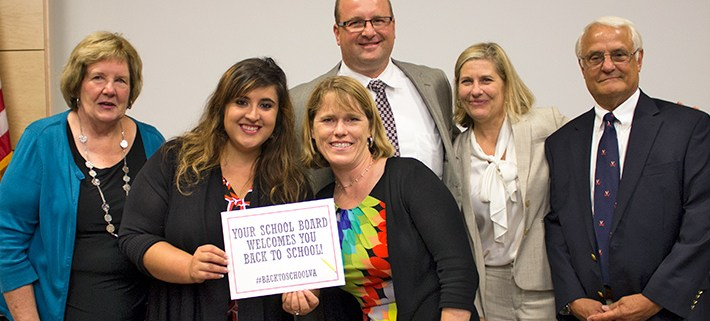 School Board members holding up a sign welcoming students and staff back to school.