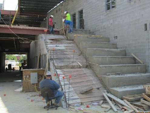 Construction workers working on the gathering stairs inside the new 4th middle school