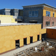 South elevation of the theater classroom and art room noting brickwork along the base of the walls, and exterior framing, sheathing, and spray foam insulation at the high wall