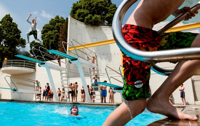 Carter Werner, 12, of Fargo, N.D., leaps from the high-diving board at the Island Park Swimming Pool in Fargo on Monday, June 8, 2015. Werner hit the water with friends during the 86-degree day.