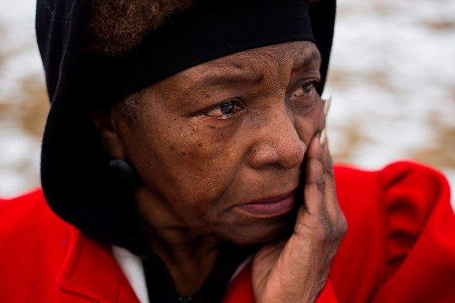 """Gail Morton, 64, of Flint, Mich., sobs as she watches protestors gather following a scheduled march with the Rev. Jesse Jackson that made it's way from the Metropolitan Baptist Tabernacle Church over a mile to the front of the the City of Flint Water Plant, on Friday, February 19, 2016. """"As a small child growing up you could almost see what our parents went through. We didn't have the rights. We didn't even have the rights to live in certain neighborhoods,"""" Morton said. """"I am so proud today, I mean, I am really proud.""""  Brittany Greeson"""