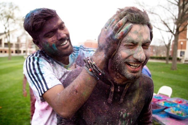 Chirag Ar, a sophomore from India, sneak attacks Saudi Arabian student, Mustafa Almarhun with handfuls of brightly colored holi powder during the 2016 Holi Festival hosted by the Indian Student Association on South Lawn at Western Kentucky University on March 19, 2016. Holi is a Hindu celebration of good over evil that is traditionally celebrated in India and southeast Asia.    Photo by Alyse Young