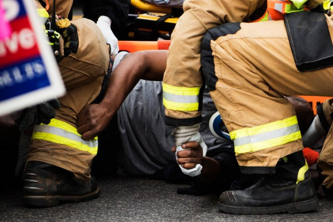 """A man is helped by emergency workers after being hit by a car on Tuesday, Nov. 8, 2016, at on Highway 31W in Bowling Green, Ky. Campaigners lined the corners of the intersection where the man was hit. """"I didn't see him"""" said the driver while talking to police. The man that was hit moved onto the street as people were campaigning on a nearby sidewalk."""