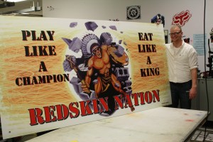 """Student Nathan Lynch poses proudly with his """"Play like a Champion/Eat like a King - Redskin Nation"""" sign that will be displayed in Burger King"""