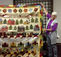 """Speaker Joyce Lawyer shows one of her many quilts she spoke about during her program, """"Around the Block."""""""