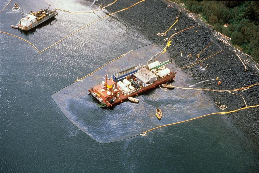Robotnicy czyszczący plaże i barka zbierająca wypłukaną ropę