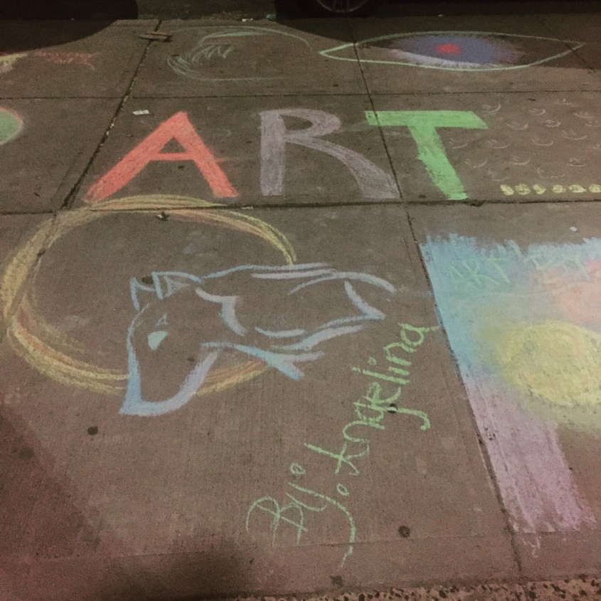 Sidewalk chalk drawings: Wolf's head and full moon, blinking eye, and the artist's statement