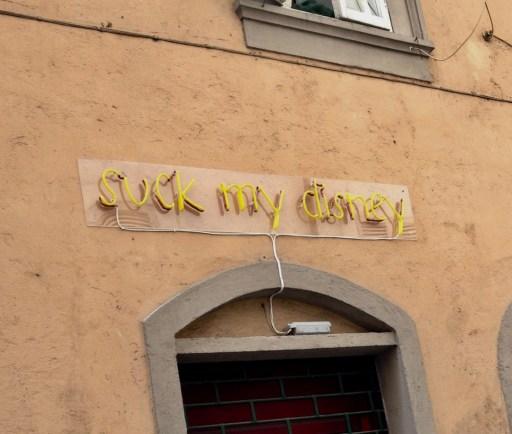 Neon sign above shop door: Suck my disney
