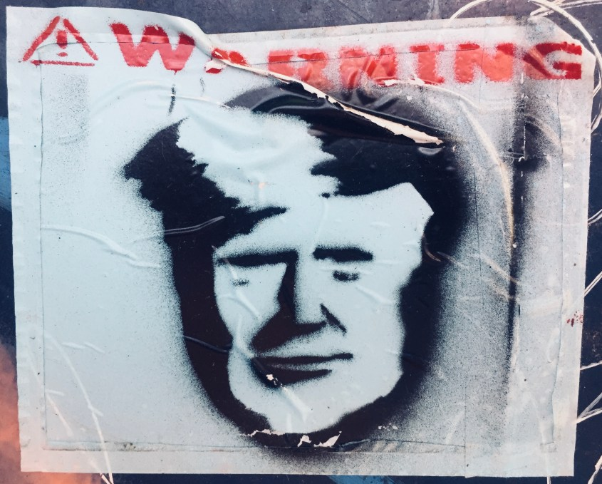 Sticker found on the Streets of Brooklyn: ! Warning above the stencil image of Trump's face