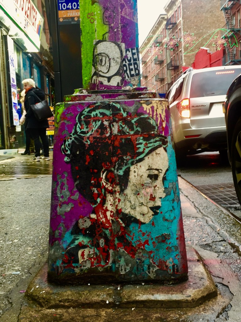 A lamp post with several layers of artwork, a painting of a woman revealing earlier work, A big eyed hoodie boy and a line drawing of a hatted man ordering you away, all over remnants of still earlier work.