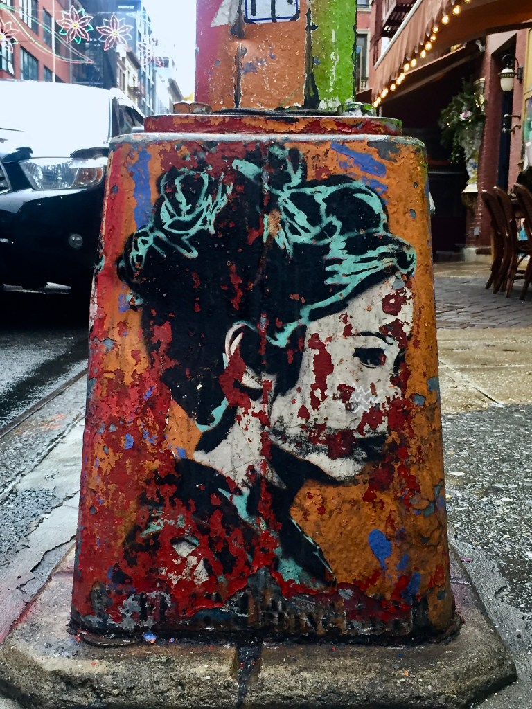 A lamp post with layers of artwork, a painting of a woman over an orange background, revealing earlier work: a decayed beauty, like much of NYC