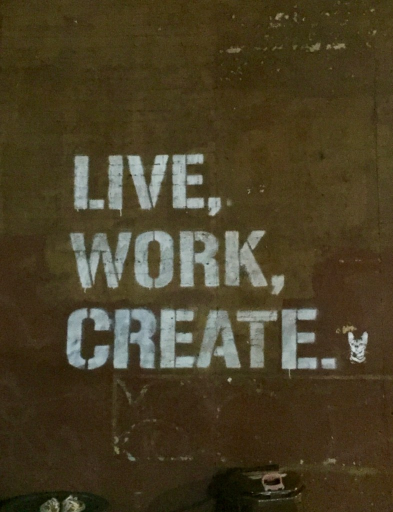 "White stencil of ""LIVE,WORK,CREATE.""  with a small kitty's head on a flat brown wall: sums up the mood in and many neighborhoods in #Brooklyn . #streetart #Stencil"