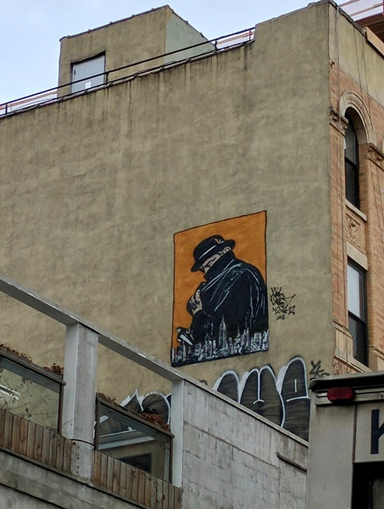 Mural of a shady looking guy, pulling the  color of his coat up, with his hat pulled down, behind the NYC Skyline on a field of reddish orange.