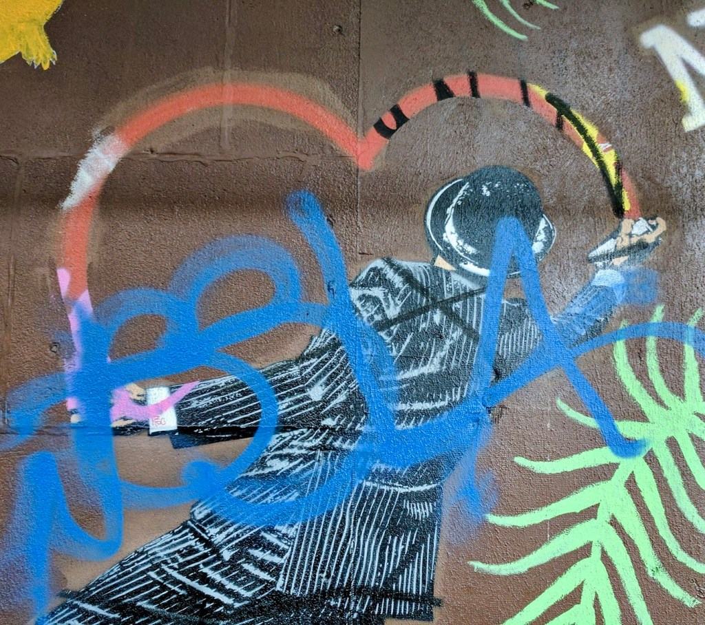 A graffiti figure in pinstriped suit and bowler paints the top of a graffiti heart. His spray paint though seems to reveal rather than cover.