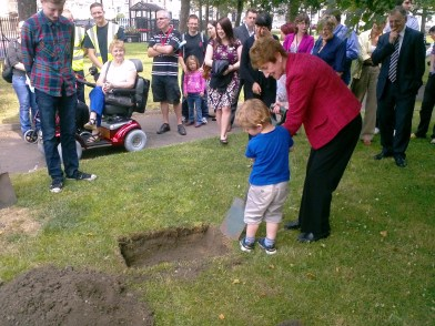 Mayor Norma Redfearn has a helping hand from youth in burying the time capsule