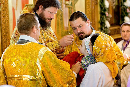 The Eucharist - Priest communing a young child.