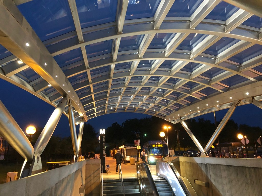 A stainless steel canopy at a Metrorail stop at night.
