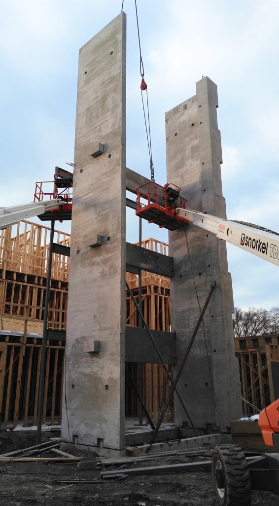 Ironworkers connecting a precast beam in a stair tower from lifts