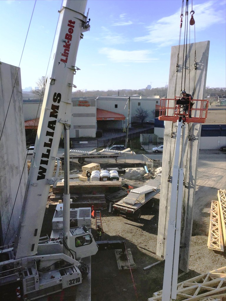 Crane lifting a precast wall panel