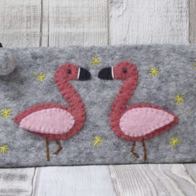 A fairtrade purse is felted in a soft grey with two tone pink flamingos handstitched to the front.
