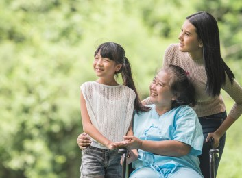Daughter and granddaughter with mother in wheelchair