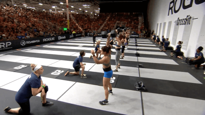 The first heat of elite women start into their dumbbell snatches. They'll follow with nine handstand push-ups.