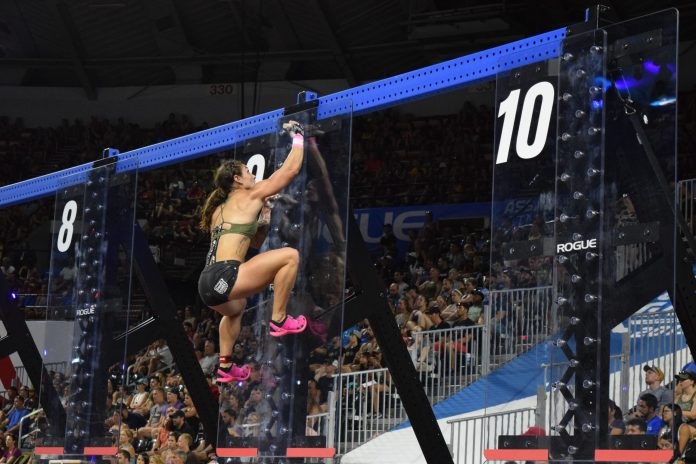 Bethany Shadburne climbs pegboards in the coliseum at the 2019 CrossFit Games.