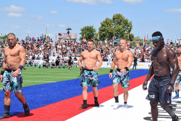 Chandler Smith walks off the field with Jacob Heppner and Scott Panchik after an event at the 2019 CrossFit Games