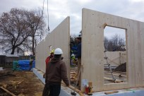 The long north wall is hoisted into place. Each exernal wall and ceiling has an airtight gasket on the edge