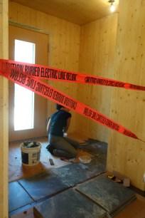 Anne works on tiling the entrance