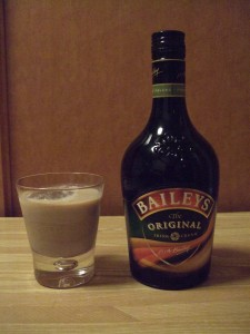 Bottle of Baileys Original and a glass with Baileys and ice