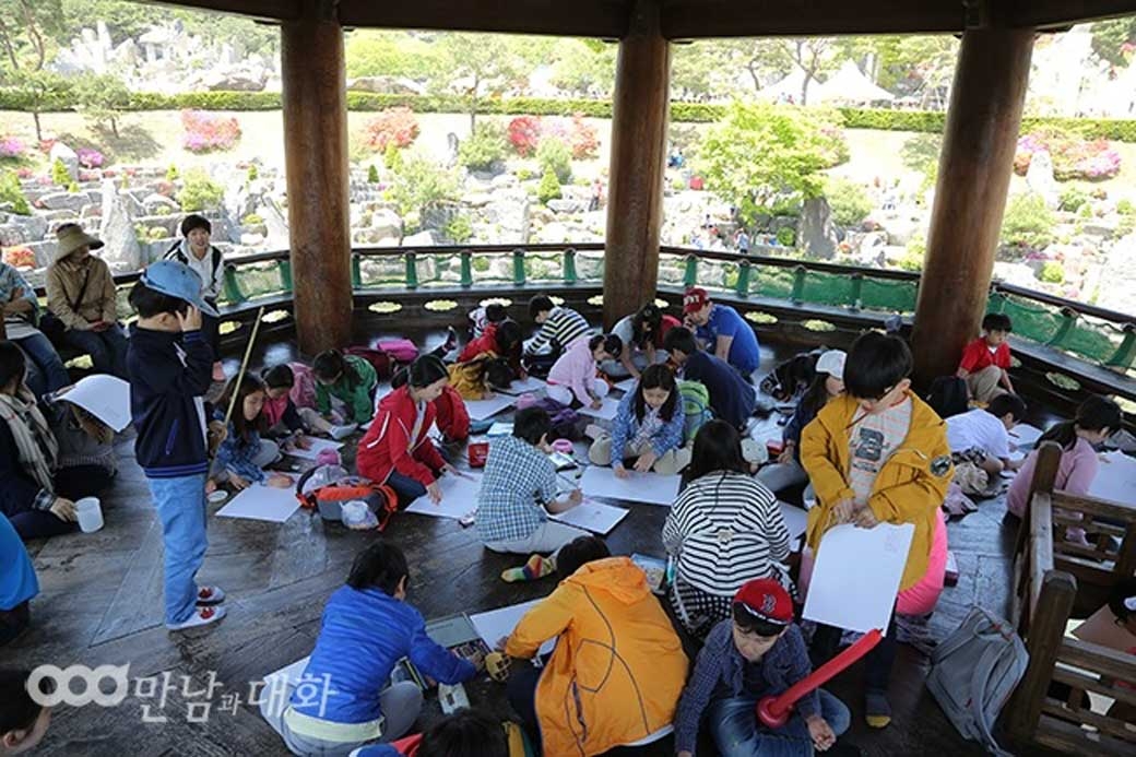 A bunch of children draw and color while sitting under the shade of the pavilion in Wolmyeongdong lake