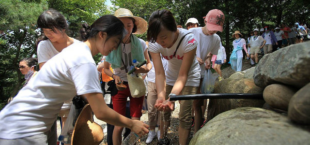 A group of hikers drink water from a natural springs in Wolmyeongdong