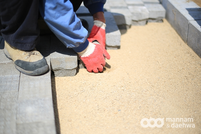 A worker places the bricks one by one to form the pavement in Wolmyeongdong