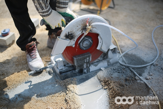 A worker uses an electric saw to cut out the cement bricks used to make the sidewalk in Wolmyeongdong