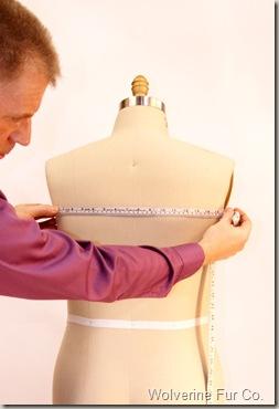 Measuring back of fur coat.
