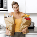 Woman carrying two very full paper bags filled with groceries