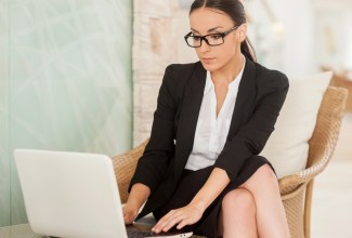 Confident and successful business lady. Confident young woman in formalwear working on laptop while sitting at the comfortable chair