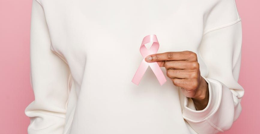 woman in a white hoodie holding a pink ribbon