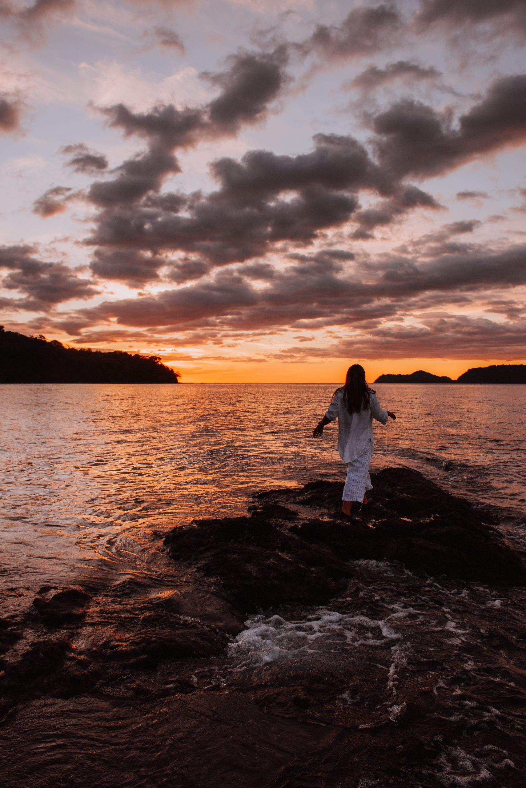 girl on rocks at sunset in costa rica by the ocean