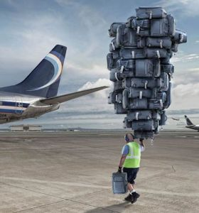 man carrying suitcases - source visualnews