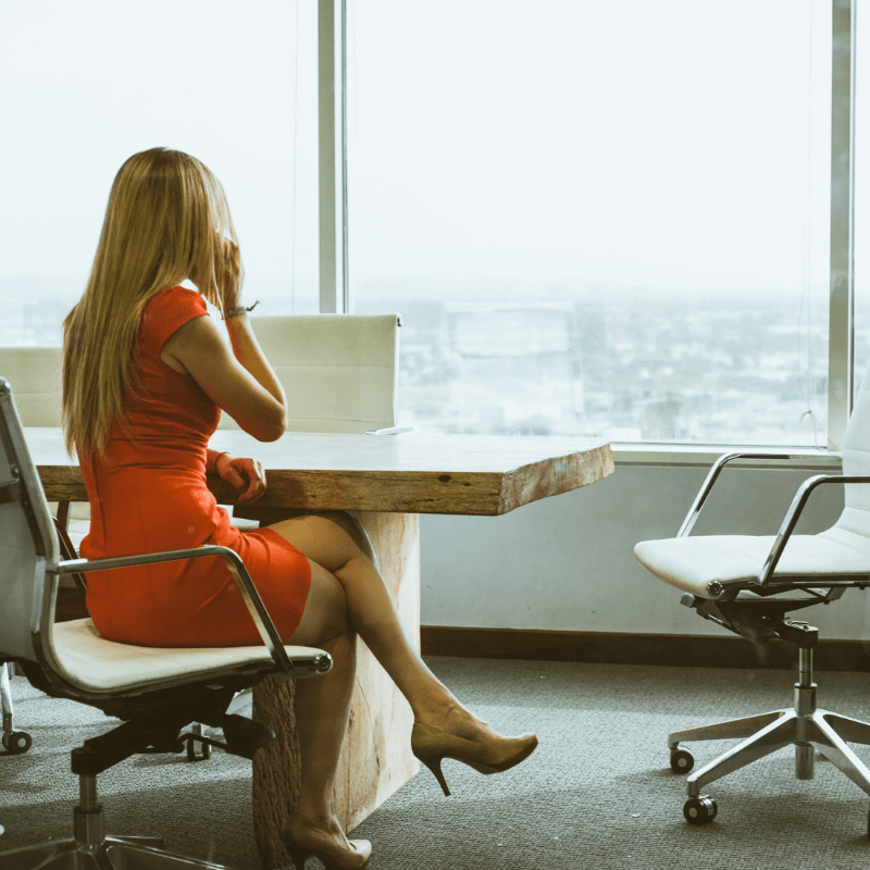 Woman sitting in chair while talking on the phone and looking out of the window